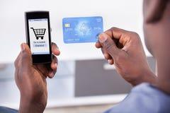 Carta di credito e telefono cellulare della tenuta della persona Fotografie Stock