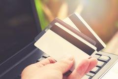 Carta di credito ed usando credito di compera online e la carta di debito di pagamento facile del computer portatile a disposizio fotografie stock