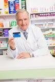 Carta di credito senior sorridente della tenuta del farmacista Fotografie Stock