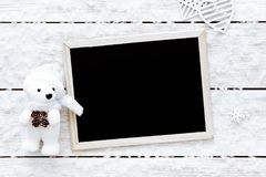 Carta di giorno di biglietti di S. Valentino, fiocchi di neve, cuori, orso del giocattolo e lavagna su fondo di legno bianco, vis Fotografia Stock