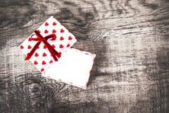 Carta di giorno di biglietti di S. Valentino con i contenitori di regalo e cuori aperti e costola rossa Immagine Stock