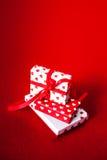 Carta di giorno di biglietti di S. Valentino con i contenitori ed i cuori di regalo su rosso ritenuto indietro Immagine Stock