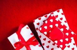 Carta di giorno di biglietti di S. Valentino con i contenitori ed i cuori di regalo su rosso ritenuto indietro Fotografie Stock