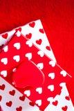 Carta di giorno di biglietti di S. Valentino con i contenitori ed i cuori di regalo su rosso ritenuto indietro Fotografia Stock Libera da Diritti