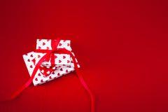 Carta di giorno di biglietti di S. Valentino con i contenitori ed i cuori di regalo su rosso strutturati Fotografia Stock