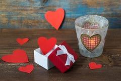 Carta di giorno di biglietti di S. Valentino, cuori rossi in un contenitore di regalo e candela bruciante con i cuori su fondo di Immagini Stock