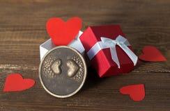 Carta di giorno di biglietti di S. Valentino, cuori rossi in un contenitore di regalo e cioccolato con i cuori su fondo di legno Fotografia Stock