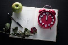Carta di giorno di S. Valentino con le bei rose rosse e taccuino Fotografie Stock
