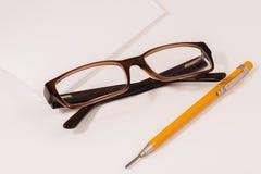 Carta di Glassses, della matita e del taccuino Fotografia Stock