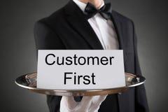 Carta di Holding Customer First del cameriere sul vassoio immagini stock libere da diritti
