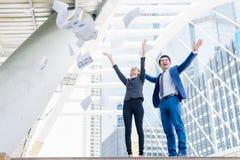 Carta di lancio asiatica della donna di affari e dell'uomo d'affari nell'aria ad allegro e celebrata per l'affare riuscito fotografia stock