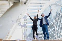 Carta di lancio asiatica della donna di affari e dell'uomo d'affari nell'aria e nel sollevare su due mani al celebrato a per rius immagini stock libere da diritti