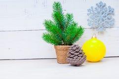 Carta di natale con l'albero, il fiocco di neve e la palla di abete su fondo di legno Fotografia Stock