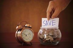 Carta di parola di risparmi della tenuta della mano con la bottiglia e l'orologio sulla tavola di legno Immagine Stock