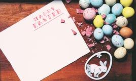 """Carta di pasqua con lo spazio della copia per il vostro testo Carta con le parole """"Pasqua allegra """", le uova e un coniglietto fotografia stock libera da diritti"""