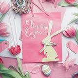 Carta di pasqua felice abbastanza pastello con iscrizione, i fiori dei tulipani, le uova e la decorazione del coniglietto, fotografie stock libere da diritti
