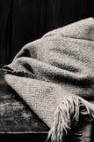 Carta di stile di concetto di inverno - sciarpa tricottata della lana sopra backg di legno Fotografia Stock