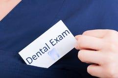 Carta di visita della tenuta della mano del primo piano con esame dentario fotografie stock