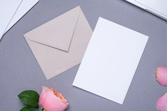 Carta e busta di regalo con la rosa rosa su fondo grigio fotografie stock