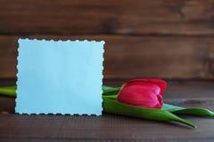 Carta e tulipano benvenuti su un fondo di legno scuro Concetto della h Immagini Stock