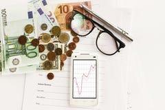 Carta e vetri della penna del calcolatore del telefono dei soldi su fondo bianco immagine stock libera da diritti
