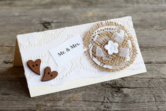Carta fatta a mano dell'invito di nozze decorata con il fiore della tela da imballaggio e del pizzo ed i cuori di legno closeup Fotografia Stock