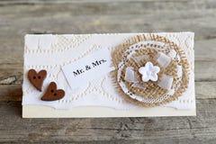 Carta fatta a mano dell'invito di nozze decorata con il fiore della tela da imballaggio e del pizzo ed i cuori di legno dei botto Fotografia Stock