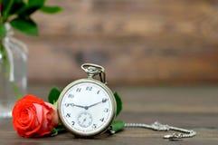 Carta felice di anniversario con il mazzo delle rose rosse e dell'orologio da tasca Fotografia Stock