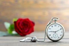 Carta felice di anniversario con l'orologio da tasca, il pendente del cuore e la rosa rossa Fotografia Stock Libera da Diritti