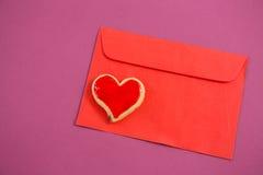 Carta felice di giorno di madre, biscotto di forma del cuore sulla busta rossa contro fondo rosa Immagini Stock