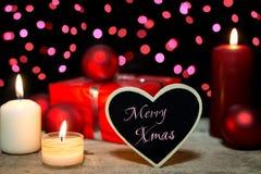 Carta festiva con le candele, un presente e palle di natale, allegri Fotografie Stock
