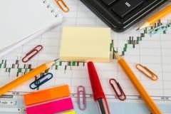 Carta financeira em um fundo branco com calculadora, moedas, penas, lápis e clipes de papel Imagem de Stock