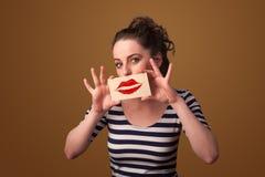 Carta graziosa felice della tenuta della donna con il segno del rossetto di bacio Immagine Stock