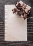 Carta inscatolata del regalo sulla versione d'annata di verticale del bordo di legno Fotografie Stock Libere da Diritti