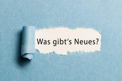"""Carta lacerata che rivela la frase tedesca per """"che cosa è nuovo? """" immagini stock"""