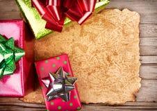 Carta lacerata su fondo di legno con i regali di Natale Fotografia Stock Libera da Diritti