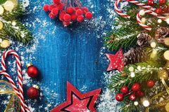 Carta o insegna di festa di Buon Natale con i rami nevosi dell'abete, i coni e le decorazioni festive Luci magiche del bokeh fotografia stock