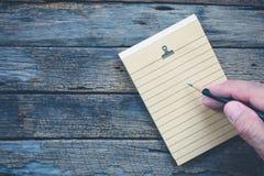 Carta per appunti della pagina in bianco con la mano e la matita, scriventi sulla pappa marrone Immagine Stock Libera da Diritti