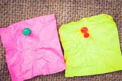 Carta per appunti rosa e verde con i perni di spinta fotografie stock