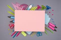 Carta rosa messa ed in bianco della cancelleria multicolore al neon per testo su fondo grigio, disposizione piana Fotografia Stock