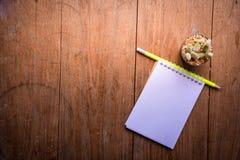 Carta succulente del taccuino e della matita in vaso sullo sfondo naturale di natura morta di legno della tavola, piante del cact Fotografia Stock
