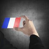Carta trasparente della tenuta della mano dell'uomo con la bandiera della Francia Immagini Stock Libere da Diritti