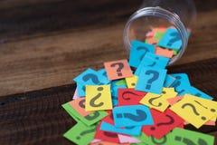 Carta variopinta con il punto interrogativo in un barattolo di plastica sulla tavola di legno fotografia stock