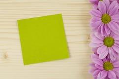 Carta verde in bianco e fiori rosa su fondo di legno Fotografie Stock