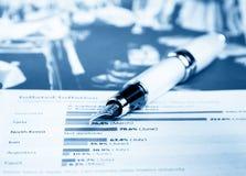 Carta y gráfico financieros cerca de la pluma del negocio Imagenes de archivo