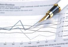 Carta y gráfico financieros cerca de la pluma del negocio Fotografía de archivo