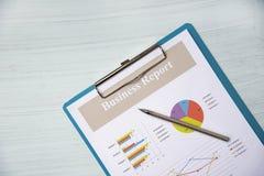 Carta y pluma del gráfico del informe de negocios en el presente del documento de papel del informe financiero en fondo de la of fotografía de archivo libre de regalías