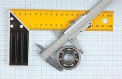 Cartabón y calibrador con el cojinete fotografía de archivo