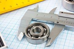 Cartabón y calibrador con el cojinete fotografía de archivo libre de regalías