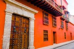 CARTAGENA, COLOMBIA 22, 2017: De stadsstraat van Cartagena met de oranje bouw en schitterende houten reusachtige deur van Cartage Royalty-vrije Stock Afbeelding